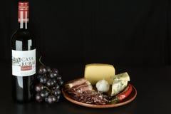 Le vin rouge espagnol, raisins, fromage bleu, a coupé en tranches le prosciutto et le salami Photos stock