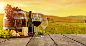 Le vin rouge et blanc a servi sur les planches en bois, vignoble sur le fond Photo libre de droits