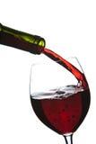 Le vin rouge pleuvant à torrents dans la glace a isolé Images stock