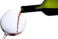 Le vin rouge a plu à torrents dans une glace Images stock