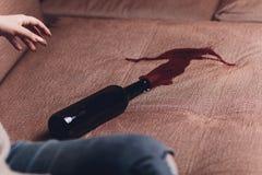 Le vin rouge s'est renversé sur un sofa brun de divan la bouteille foncée de vin rouge s'est laissée tomber photos libres de droits