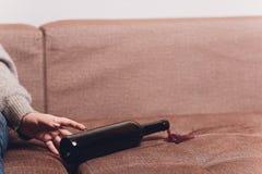 Le vin rouge s'est renversé sur un sofa brun de divan la bouteille foncée de vin rouge s'est laissée tomber photographie stock libre de droits