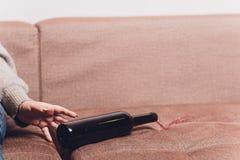 Le vin rouge s'est renversé sur un sofa brun de divan la bouteille foncée de vin rouge s'est laissée tomber photo libre de droits