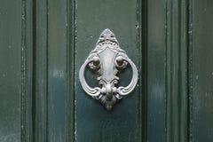 Le vintage antiqued le heurtoir de porte sur la porte verte en bois photos libres de droits