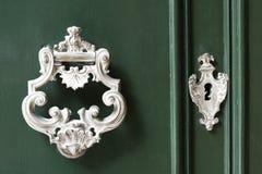 Le vintage antiqued le heurtoir de porte sur la porte verte en bois images libres de droits