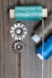 Le vintage boutonne des fleurs et des bobines avec des fils Images stock