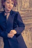 Le vintage colorized l'image des femmes d'une chevelure rouges posant contre la porte superficielle par les agents Photographie stock libre de droits