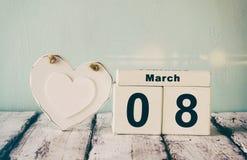 Le vintage a filtré l'image du calendrier en bois du 8 mars, à côté du coeur blanc sur la vieille table rustique Foyer sélectif Photos stock