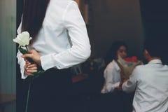 Le vintage a modifié la tonalité l'image de la femme asiatique navrée déprimée tenant une rose blanche derrière elle de retour av Photos stock