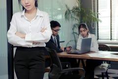 Le vintage a modifié la tonalité l'image de la jeune femme asiatique d'affaires de direction se tenant dans le bureau avec des co Photo libre de droits