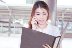 Le vintage a modifié la tonalité l'image de la jeune femme asiatique d'affaires de joli visage regardant le papier de document su image libre de droits