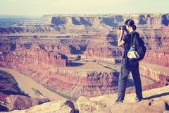 Le vintage a modifié la tonalité la femme prenant les photos d'un paysage de canyon, Etats-Unis Images libres de droits