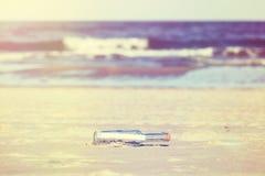 Le vintage a stylisé le message dans une bouteille sur la plage, profondeur de photos stock