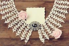 Le vintage a tricoté le collier, broche antique, roses roses, carte de papier images stock