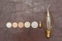 Le vintage, une petite ampoule avec des pièces de monnaie (roubles russes) se trouvent sur un fond en cuir Steampunk photos stock