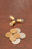 Le vintage, une petite ampoule avec des pièces de monnaie (roubles russes) se trouvent sur un fond en cuir Steampunk image stock