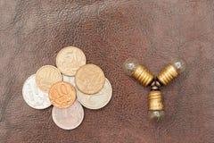Le vintage, une petite ampoule avec des pièces de monnaie (roubles russes) se trouvent sur un fond en cuir Steampunk images libres de droits
