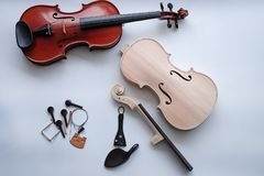 Le violon cru mis près du violon réalisé images stock