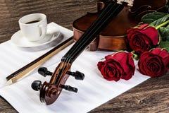 Le violon, s'est levé, café et des cahiers de musique Images stock