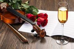 Le violon, s'est levé, verre de champagne et cahiers de musique Photo stock