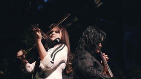 Le violoniste et le violoncelliste reculent pour soutenir sur l'étape et pour exécuter leurs pièces artistiquement banque de vidéos