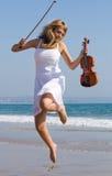 le violoniste sautent sur la plage photo stock
