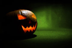 Le visage découpé du potiron rougeoyant Halloween sur le fond vert Photos libres de droits
