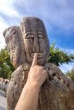 Le visage découpé en bois avec la main de femme sur des lèvres a découpé le chiffre Images stock