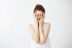 Le visage de dissimulation ennuyé de jeune jolie fille fatiguée derrière remet le fond blanc Image libre de droits