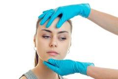 Le visage de jeunes belles filles qui examine un cosmetologist dans les gants bleus a isolé sur un fond blanc Images stock
