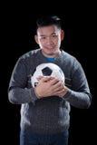 Le visage de l'amant du football tenant la boule du football a isolé le backgr noir Photo libre de droits