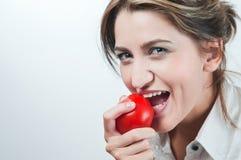 Le visage de la belle fille mangeant une tomate Image stock