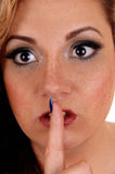 Le visage de la femme avec un doigt au-dessus de bouche Photographie stock libre de droits