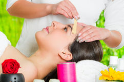 Le visage de la femme de plan rapproché recevant la pilosité faciale cirant le traitement, la main utilisant le bâton en bois pou Image stock