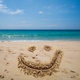 Le visage de sourire dessinent sur la plage au-dessus de la mer Photo libre de droits