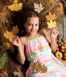 Le visage de sourire de fille d'enfant étendent des attributs en bois de chute de fond L'enfant avec de longs cheveux avec l'érab images stock