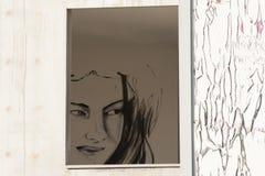 Le visage du ` s de fille dans la fenêtre d'une maison abandonnée image stock