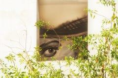 Le visage du ` s de fille dans la fenêtre d'une maison abandonnée photographie stock