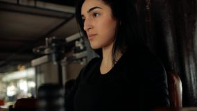 Le visage en gros plan de la fille caucasienne de brune secoue ses muscles abdominaux avec ses mains sur la barre horizontale banque de vidéos