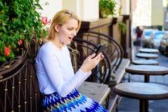 Le visage enthousiaste de femme avec le smartphone créent le rendez-vous dans le réseau social et attendent la terrasse de café d Photos libres de droits
