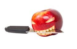 Le visage fâché est découpé sur une pomme et un couteau Photos libres de droits