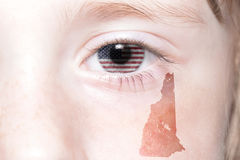 Le visage humain du ` s avec le drapeau national des Etats-Unis d'Amérique et le New Hampshire énoncent la carte Photo stock