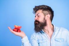 Le visage strict d'homme avec la barbe offre les festins organiques Je prends des festins pour vous L'homme offre d'essayer les f photo stock