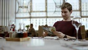 Le visiteur du restaurant seul parle au serveur ce qui il ce qui ? manger Il montre par le doigt dans le menu, travailleur fait banque de vidéos