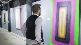 Le visiteur masculin de l'exposition de l'artiste abstrait moderne observe l'image banque de vidéos