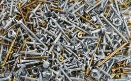 Le viti d'acciaio e d'ottone, i dadi ed i perni del metallo hanno sparso sul piano Immagini Stock