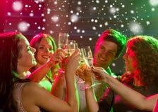 Le vänner med exponeringsglas av champagne i klubba Fotografering för Bildbyråer