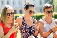 Le vänner med smartphones som sitter på gräs Arkivfoton