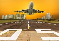 Le vol d'avion décollent de la piste avec le fond moderne de gratte-ciel Images libres de droits
