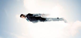 Le vol d'homme d'affaires aiment un super héros en nuages sur le ciel Photographie stock libre de droits